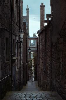 ランタンが付いている古いヨーロッパの都市の古い狭い通路エジンバライギリス