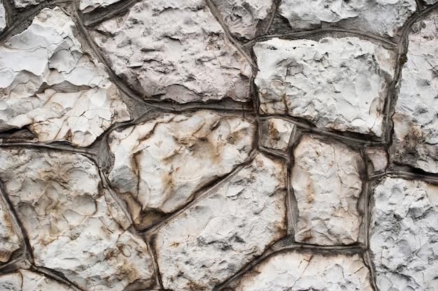 背景の古い天然石の壁のテクスチャ。