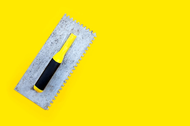 Old notched trowel on yellow background.