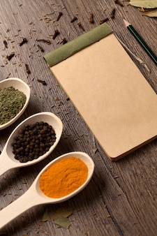 Old notebook, spices in spoons