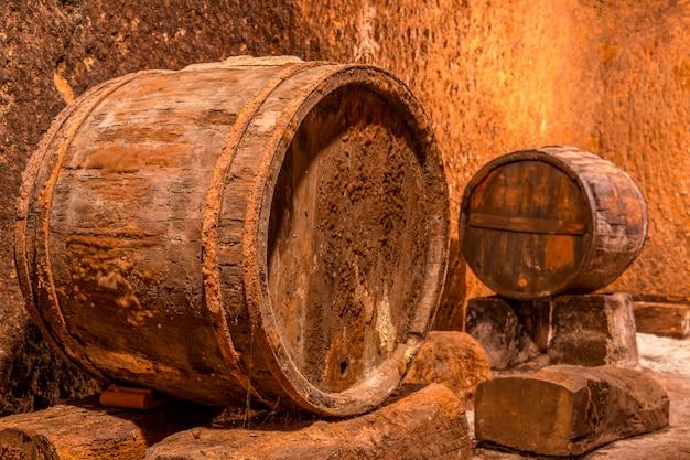 Старая дубовая бочка с ржавыми обручами. глубокий винный погреб с фактурными стенами