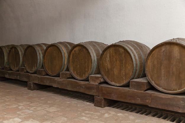 Old oak barrels lie in basement on wooden logs,old wine cellars with bottles and barrels
