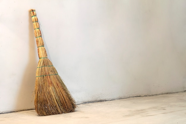 Old obsolete broom or besom leaning on the gray wall