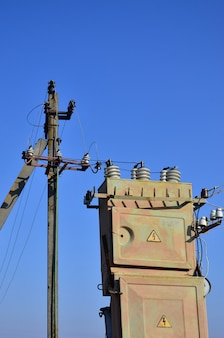 Old and obsolete electrical transformer against the background of a cloudless blue sky.