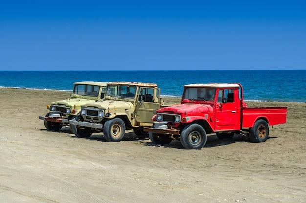 海の背景を持つ冒険に最適な古いオフロードsuv車ジープ