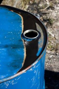 タンポポの種を閉じ込めた上に黒い油が付いた古いドラム缶