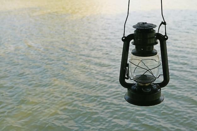 湖の波紋に対する古い石油ランプ