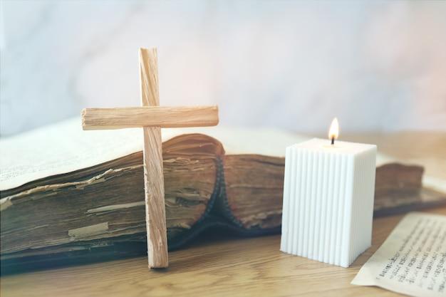 나무 십자가와 불타는 하얀 촛불이 있는 오래된 오픈 성경