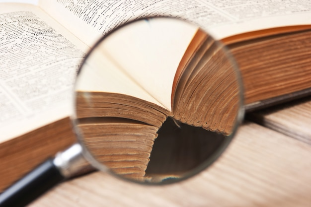 古い開いた本と虫眼鏡