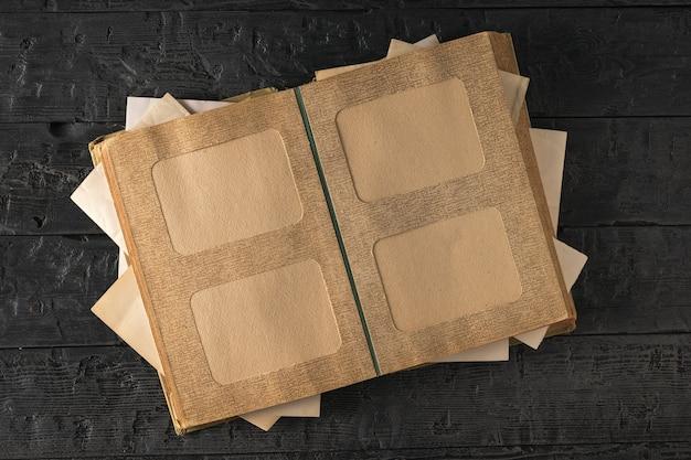 Старый открытый фотоальбом на деревянном столе. предмет семейных ценностей. вид сверху. плоская планировка.
