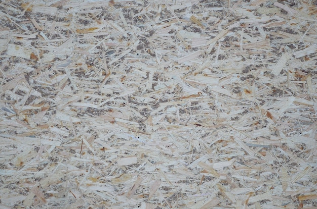 An old oriented strand board osb, fiberboard background of texture. sheet is made of brown wood chips pressed together into a wooden floor