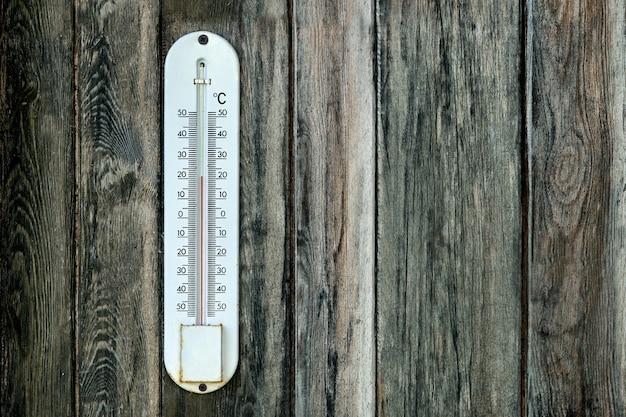 Старый наружный термометр на деревянной стене с копией пространства