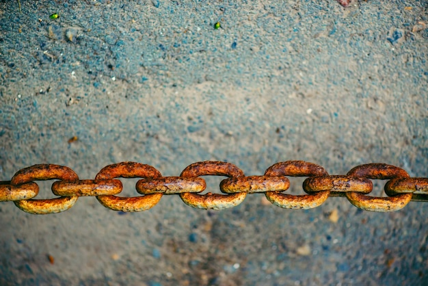 Old oxidized rusty chain hanging over asphalt close up with copy space