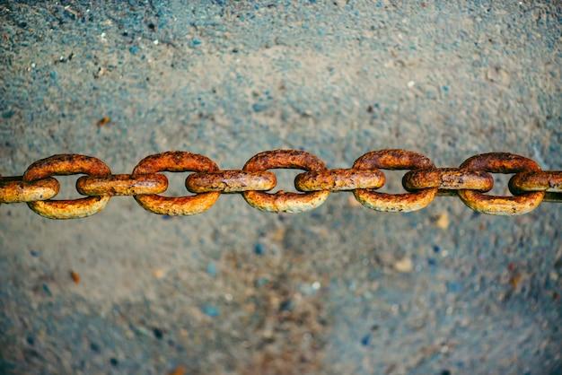 アスファルトの上にぶら下がっている古い酸化さびた鎖はコピースペースでクローズアップ。強いチェーンの太いリンクを持つ概念的な鮮やかな背景。アートワーク。