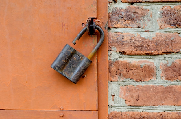 Old padlock on metal door. red brick wall