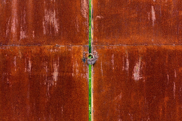 Old padlock on a rusty iron gate background