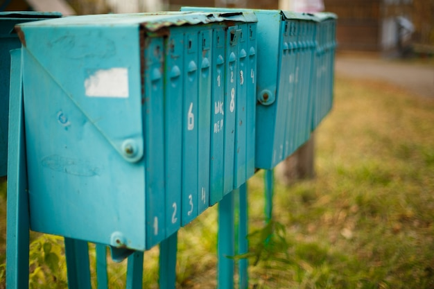 Old painted vertical metal mailboxes outside on sunny day