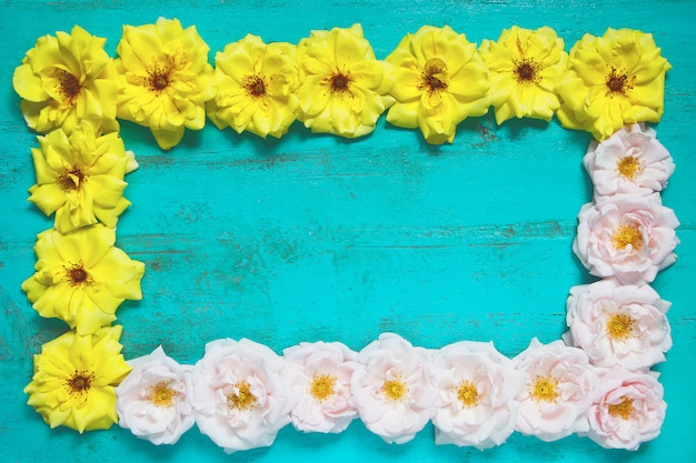 Old painted wooden table  with fresh yellow and pink garden roses lying as a frame.