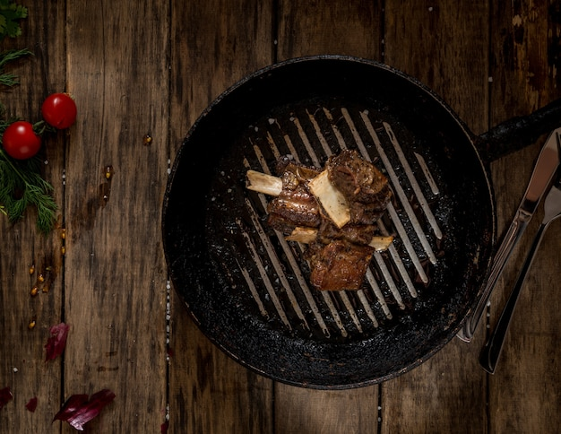 In old pan fried meat with bone on wooden background, top view