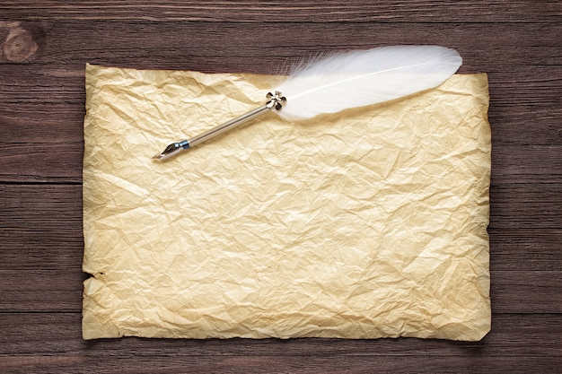 Old paper on  brown wood texture with white feather