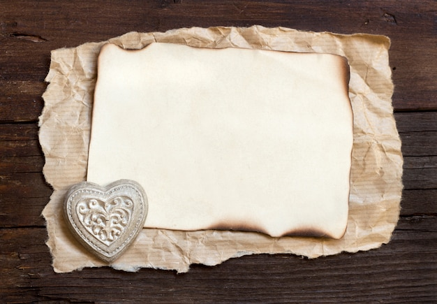 Old paper and  a heart on a brown wooden background