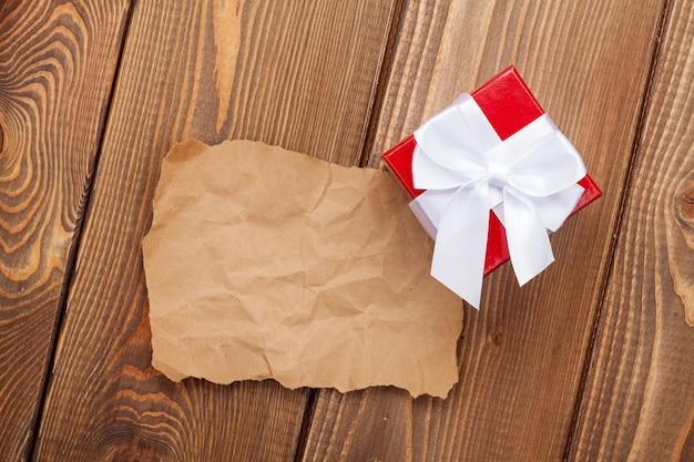Кусок старой бумаги для копирования пространства и подарочная коробка ко дню святого валентина на деревянном фоне