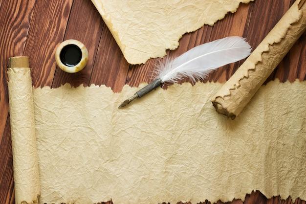 コピースペースを持つ木製の紙の上の古い紙、スクロール、羽ペン