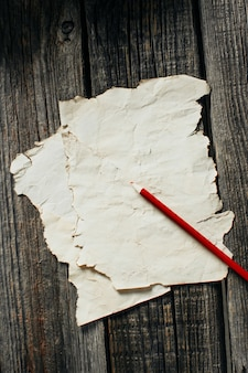 Old paper sheet on old wooden wall, lying next to a red pencil