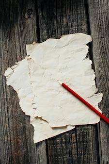 赤鉛筆の横にある古い木製の壁に古い紙シート