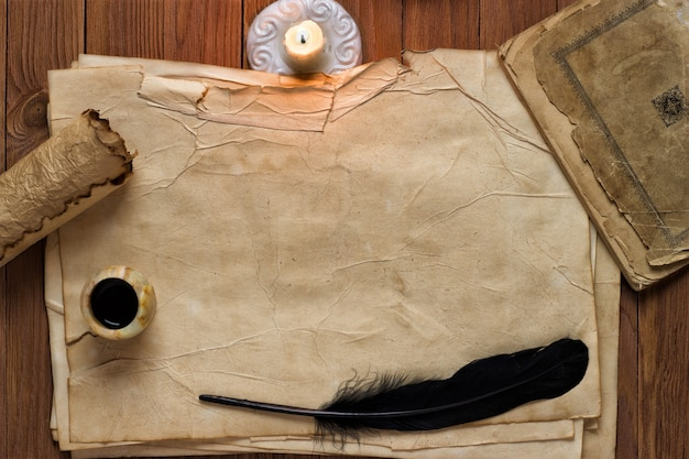 Old paper with  candle and black quill, blank background for text