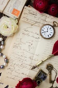 Старая бумага с пятнами чернил и старое письмо со старинными часами и пером
