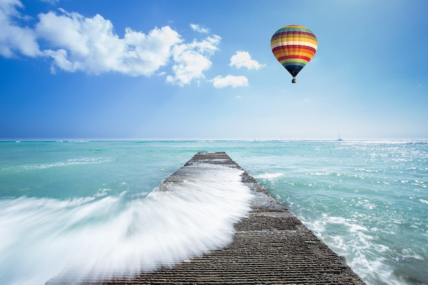 Old pathway into the sea hit by sea wave with hot air balloon over