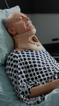 Старый пациент сидит в больничной койке с воротником на шее
