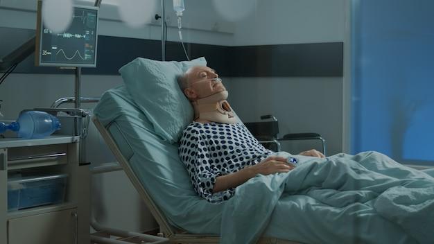 Старый пациент с шейным воротником, лежащим в больничной палате