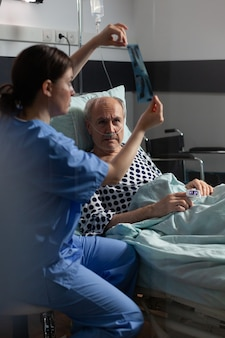 Old patient with lungs illness breathing using oxygen mask laying in hospital bed, listening nurse showing x-ray explayning diagnosis before surgery