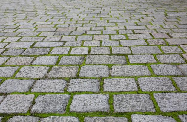 遠近法で草と古い舗装された石。クローズアップショット