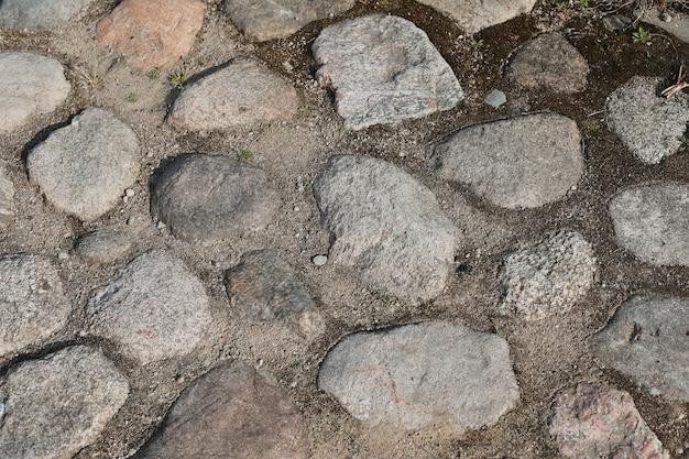 Старый тротуар из различных камней и гальки гранж каменный фон