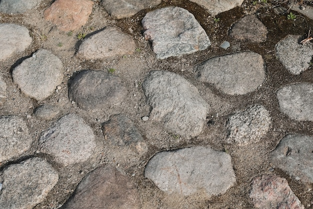 Old pavement made with various stones and pebbles grunge stone background