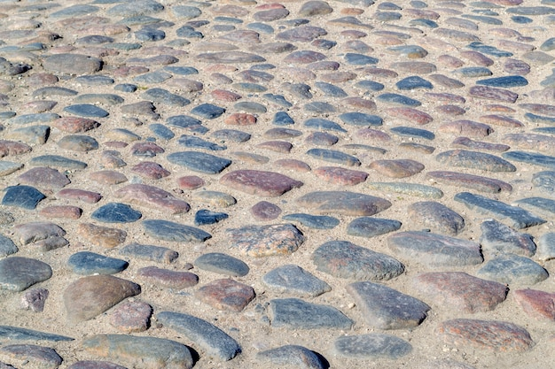 The old pavement. round stones paving stones on the street. road of stones