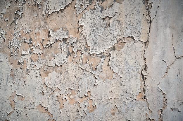 側面の明るい日光の下で壁に古い剥離石膏