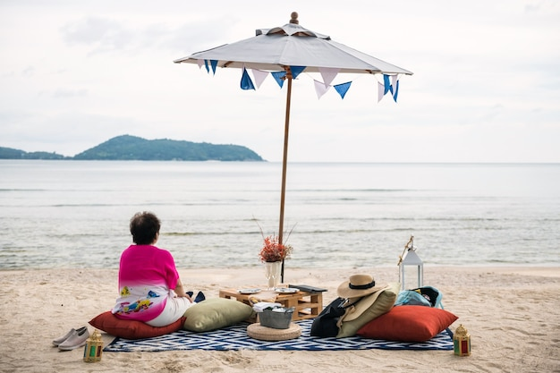 Old pension woman sit on beach picnic in phuket, thailand