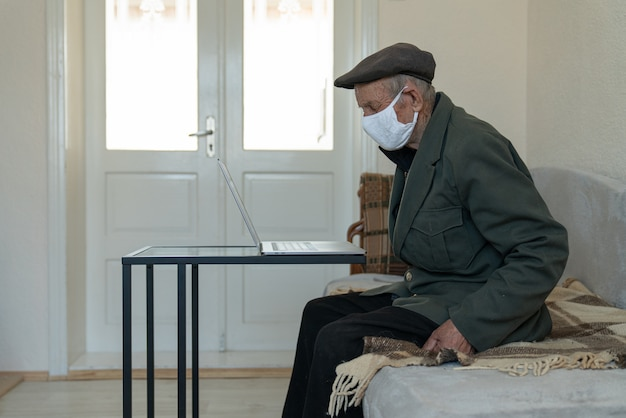 Old pensioner man in protective face medical mask sitting on the sofa at home near the work table with laptop