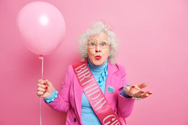 老人とお祭りのコンセプト。しわのある美しい女性の年金受給者は唇を丸く保ち、手のひらを膨らませた風船を持ち上げる 無料写真