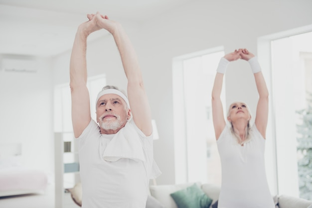 Old people doing physical exercises at home