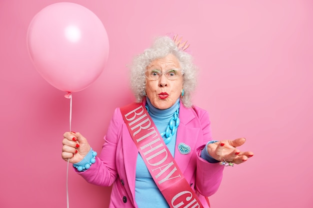 Old people and festive occasion concept. beautiful wrinkled woman pensioner keeps lips rounded raises palm holds inflated balloon
