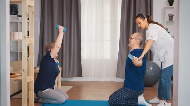 理学療法士の助けを借りた高齢者の理学療法。在宅支援、理学療法、老人の健康的なライフスタイル、トレーニング、健康的なライフスタイル