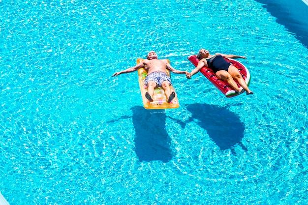 老人の年配のカップルは、青いプールでリラックスして眠ります。澄んだ水は、トレンディな色のインフレータブルマットレスリロの上に横たわり、永遠に一緒にライフスタイルのコンセプトを愛して手を取ります