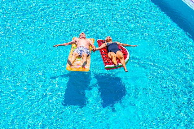 Old people senior couple relax and sleep on the blue swimming pool clear water lay down on trendy coloured inflatabler mattress lilos and taking hands with love for forever together lifestyle concept