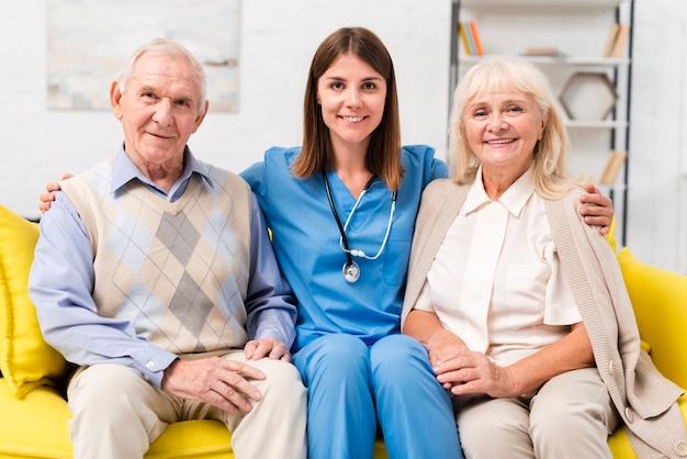Old people sitting on yellow sofa with heir nurse
