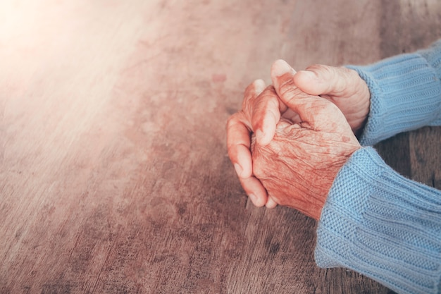 The old person's praying hand. concept: hope, belief, dramatic loneliness, sadness, depression, cry, disappointed, healthcare, pain.
